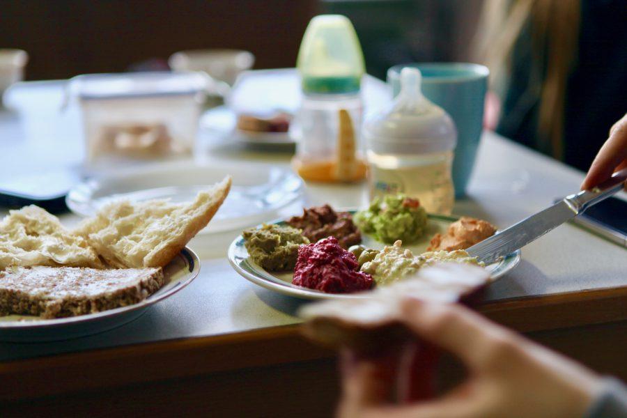 Ein Teller mit veganen Pasten, im Hintergrund stehen zwei Babytrinkflaschen auf dem Tisch.